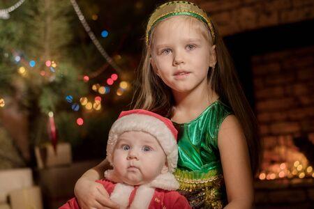 小さな女の子と赤ちゃんサンタ クロースがクリスマスを祝う