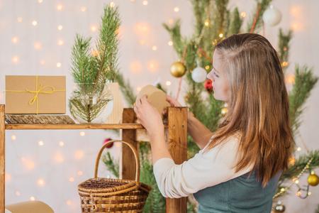 美しい少女がクリスマスのための部屋を飾る