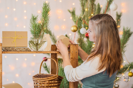 beautiful girl decorate the room for Christmas Standard-Bild