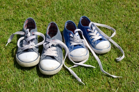 Two pairs of old sneakers on grass background photo