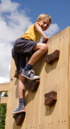 Boy scaling a climbing wall