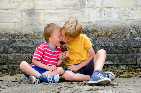 Two boys sharing an ice lolly photo