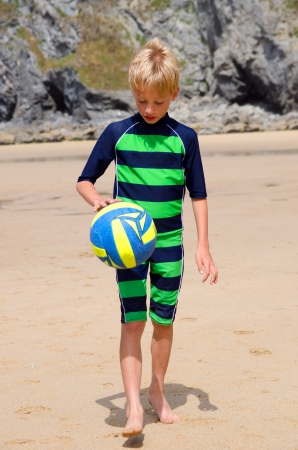 Boy playing with volleyball on a beach photo