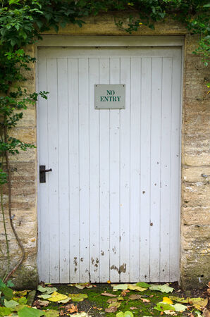 No entry sign on weathered garden door photo