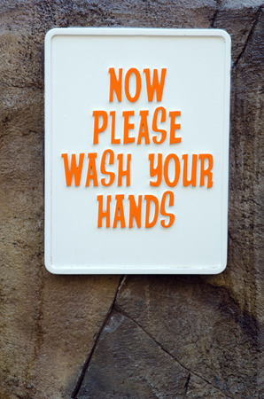 Wash your hands sign on stone wall photo