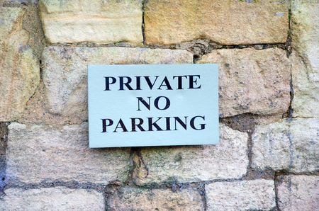 Private no parking sign on stone wall Stock Photo