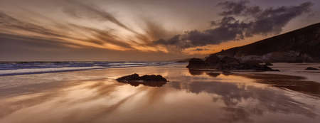 Sunset reflections on Whitsand Bay, Cornwall, UK photo