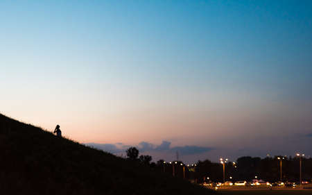 A boy with a mobile phone walks up a hill in the a city at evening