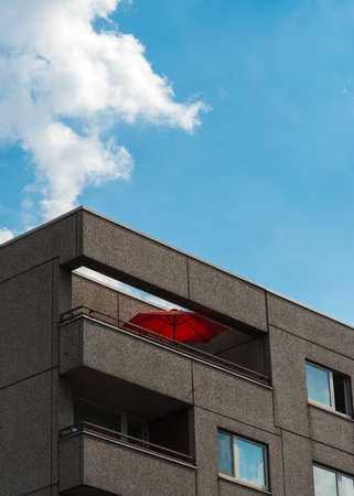 The red parasol on the balcony on the apartment block
