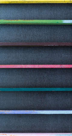 Colorful metal bars in front of a black background in close-up