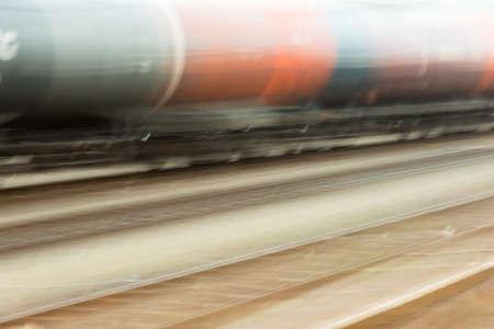 Un tren de mercancías con vagones naranjas y azules pasa rápidamente