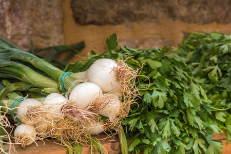 A bunch of leek onions next to the parsley