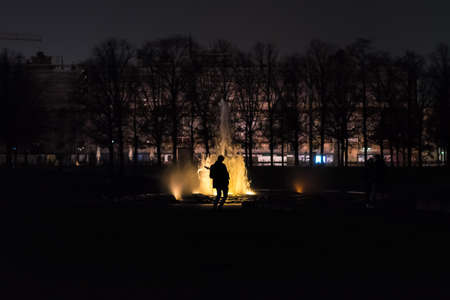 A man plays guitar at night at the fountain in berlin, germany
