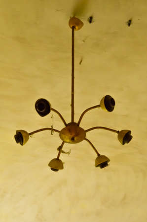 An old broken chandelier on a yellow ceiling