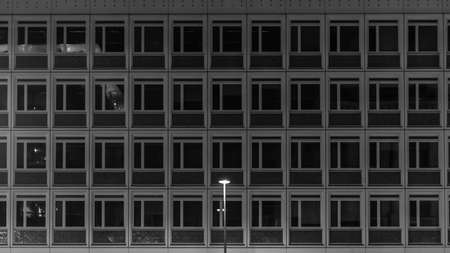 A single street lamp stands in front of a prefabricated building. Berlin, Germany.