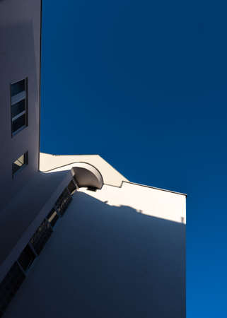 Daylight hits the white facade of a house