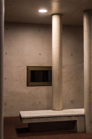 Two pillars and a black window with a white bench