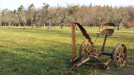 An old rusty mower on a green meadow 写真素材