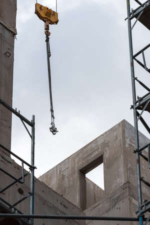 Crane hooks and scaffolding in front of an unfinished building in Berlin 写真素材