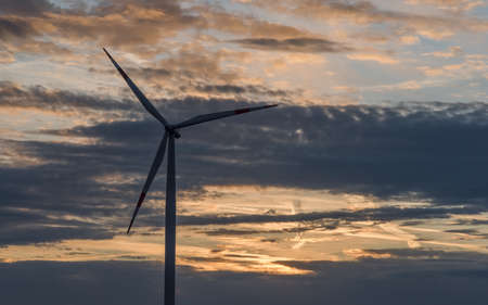 A silhouette of a wind turbine in front of a cloudy sky with sunrise