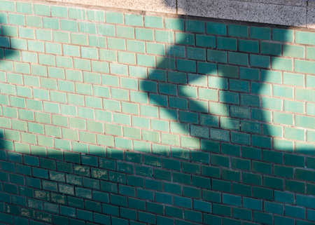 Silhouette of a lower body of a man running on a turquoise wall
