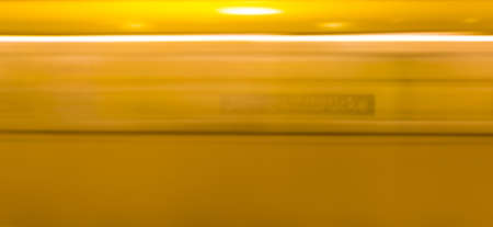 A yellow subway enters the train station