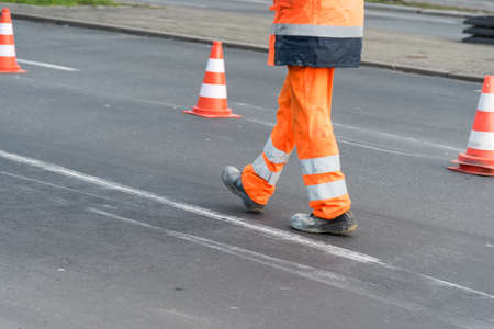 A road worker walks on the street with cones in the background
