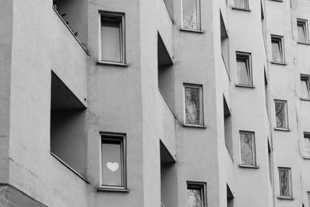 Heart behind the window of an apartment building in black and white