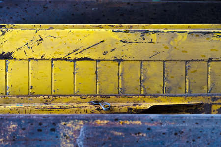 Metal spring on a yellow steel plate