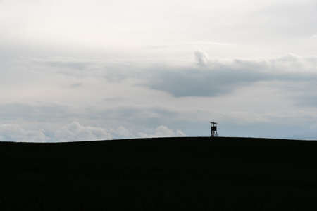 Deer stand as a silhouette in front of a cloudy sky