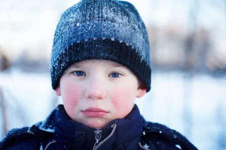 crying boy: El ni�o llorando triste con ojos azules en ropa de invierno