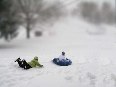 Heres two children enjoying a nice afternoon of sleigh riding. photo