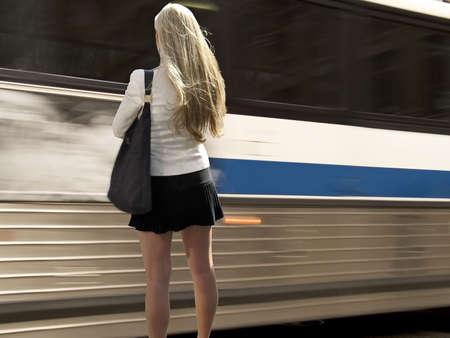 Una bella bionda donna sta dietro l'angolo come un autobus da zoom. Archivio Fotografico
