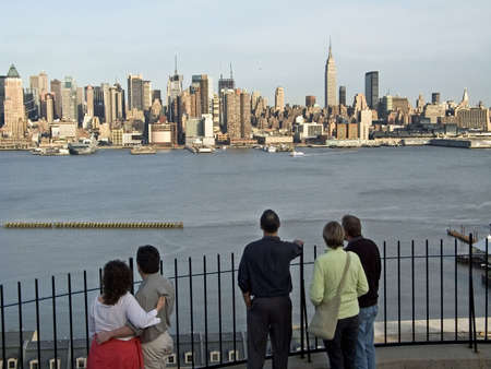 Some people are enjoying the view of The New York City skyline from a riverside park in New Jersey.