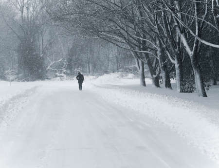 duotone: This is a blue duo-tone shot of a person walking down a country road during a snow storm. Stock Photo