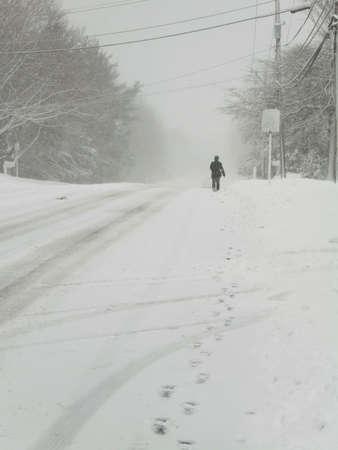 Dies ist ein Bild von einer Person zu Fuß eine Straße in einem großen Sturm Schnee.