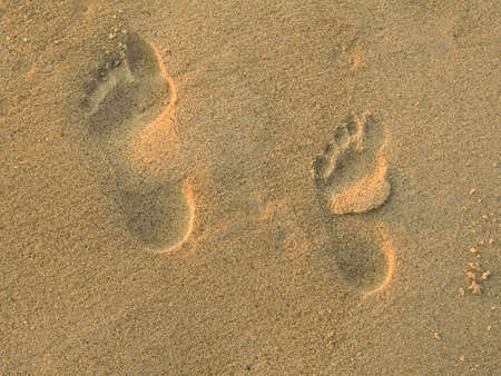 adult footprint: A childs and an adult footprint in the sand. Stock Photo
