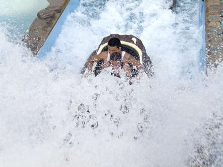 A father and child ride a soaking wet water log flume at an amusement park.