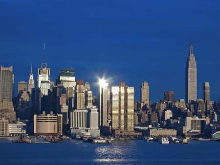 Die New Yorker Skyline spiegelt die Sonne am späten Nachmittag über dem Hudson River.