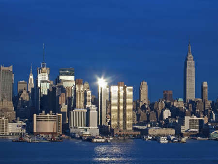 reflects: The New York city skyline reflects the late afternoon sun over the Hudson River.