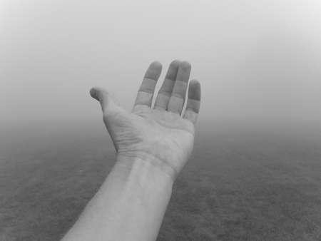 This is a B&W shot of a hand reaching out against a foggy background.