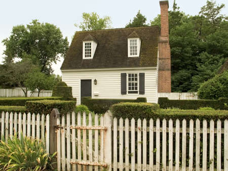 A small rural cottage with a white picket fence. photo