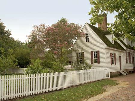 Eine kleine alte koloniale Haus mit einem weißen Lattenzaun.