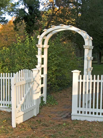 A white garden gate and picket fence along with a cobblestone walkway. photo