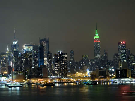 The New York City skyline with the Empire state building in red and green for the holidays.