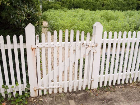An old white picket fence and garden gate. Stock Photo