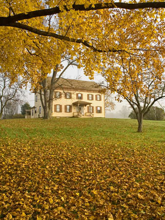 An old building in Monmouth Battlefield State Park in New Jersey framed in  golden Fall colors.