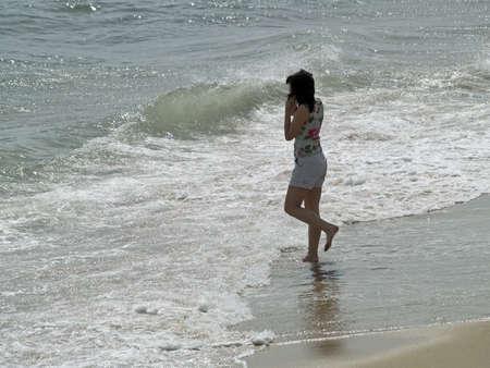 cel: Una giovane donna colloqui su un telefono cel in spiaggia.