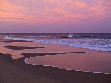 A beautiful sunset reflects in the surf along the Jersey shore. Stock Photo