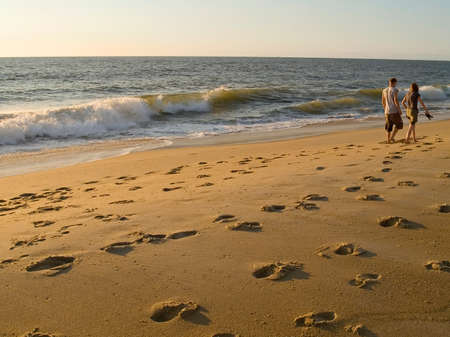 A young couple walks along the beach in Ocean City, Maryland. 写真素材